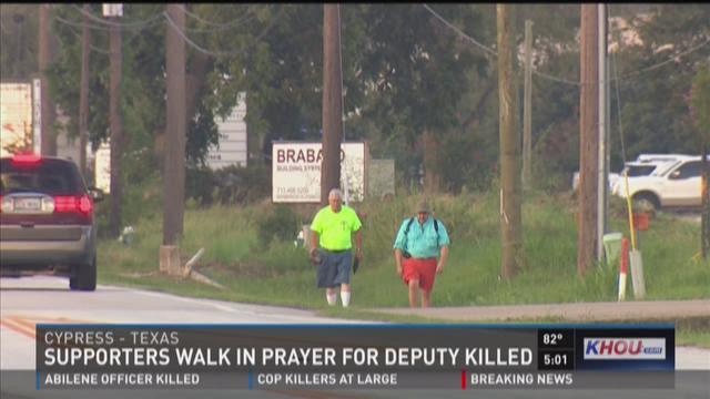Supporters walk in prayer for deputy killed